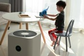 air purifier in living room with kid playing inside home